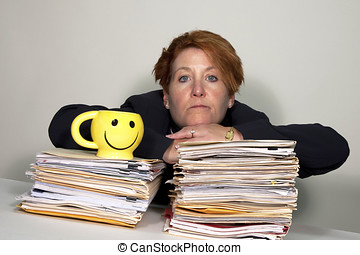 Woman sitting on her overflowing work pile with a yellow...