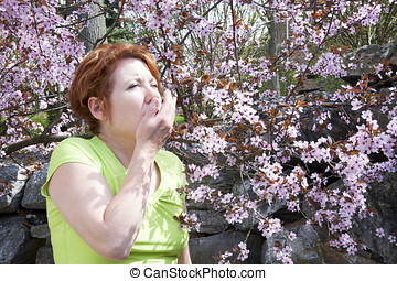 Woman sneezing while standing amid pink flowers