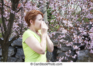 woman blowing her nose into a tissue while standing amid...