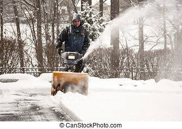 Man pushing snow blower up a driveway