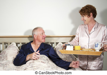 Man being served breakfast in bed by his wife.