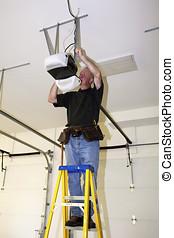 Man standing on a ladder fixing a mechanical garage door...