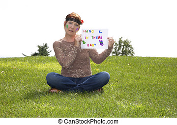 Aging hippie holding a sign with a message for the younger generation:  Hang In There Baby
