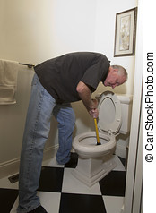 Man with plunger fixing blocked toiler
