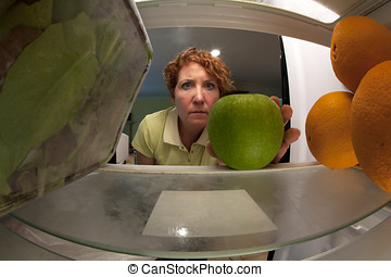 View from inside refrigerator of a woman selecting an apple...