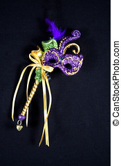 Purple, green and gold mardi gras mask on sceptar isolated...