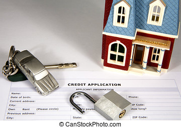 Miniature house and car with keys on top of a credit...