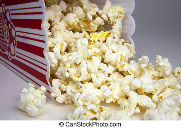 Popcorn container on its side with popcorn kernals spilling out.