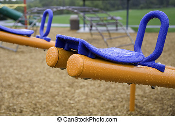 Blue and orange seat on a teeter totter in a rain soaked,...