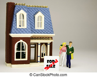 Figurine of a young couple in front of a house with a FOR SALE - SOLD sign.