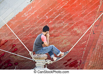 Asian man on the phone in front of the bow of a schooner...