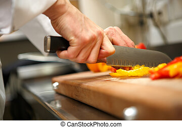 closeup on hands cutting yellow pepper on professional...