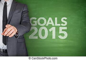 Goals 2015 on blackboard with businessman hand pointing