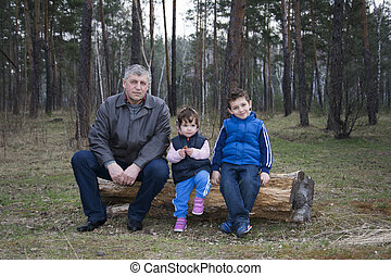 Spring in the pine forest sitting on a log with his...