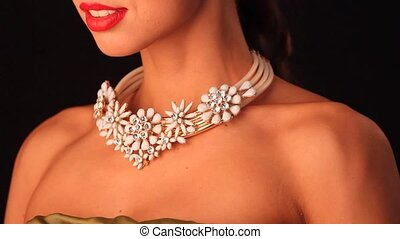 necklace on Indian woman's neck on dark background