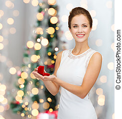 smiling woman holding red gift box with ring - winter...