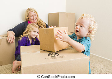 Young Family In Empty Room Playing With Moving Boxes -...