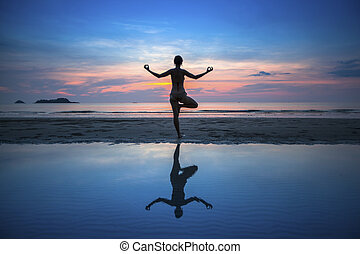 Silhouette of woman practicing yoga during sunset at seaside.