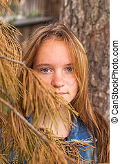Portrait of a young beautiful girl in a pine forest.