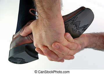 Hands boosting a shoe - Hands boosting a male shoe on white...