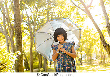 Happy Asiangirl holding umbrella in the park outdoor with...