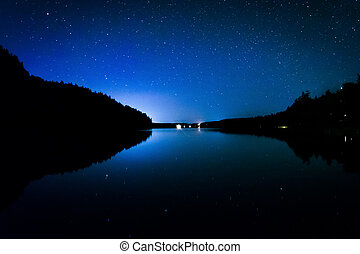 Stars in the night sky reflecting in Echo Lake, at Acadia...