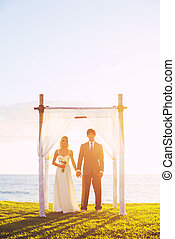 Tropical Sunset Wedding by the Ocean, Bride and Groom on...