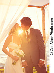 Sunset Wedding. Bride and Groom Kissing at Sunset. Romantic...