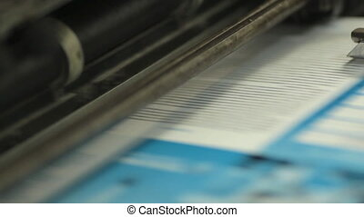 Close-up of colorful printing of leaflets at printing house...