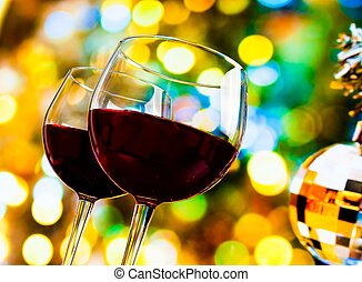 two red wine glasses against colorful bokeh lights and...