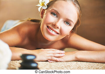 Happy client - Smiling girl looking at camera while lying in...