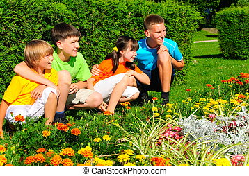 Cousins by flower garden - Four cousins together in the park...