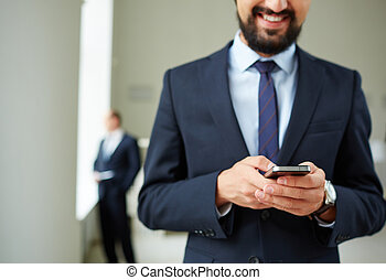 Mobility in business - Close-up of young businessman using...