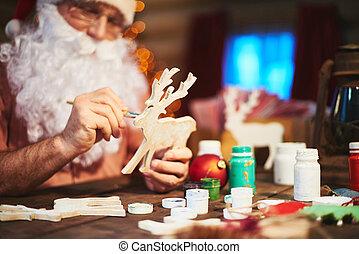Painting wooden deer - Senior Santa man painting wooden deer...