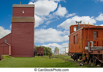Grain Elevator With Train - A grain elevator looming in the...
