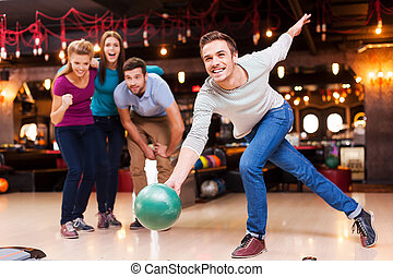 He is a winner. Handsome young men throwing a bowling ball...