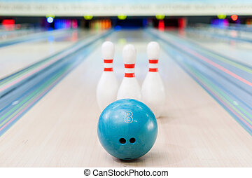 Bowling game. Close-up of blue bowling ball lying against...