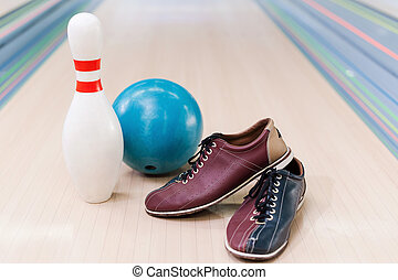 Bowling equipment . Close-up of bowling shoes, blue ball and...