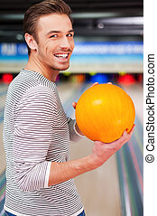 Hoping for a strike. Cheerful young man looking over shoulders and holding a bowling ball while standing against bowling alleys