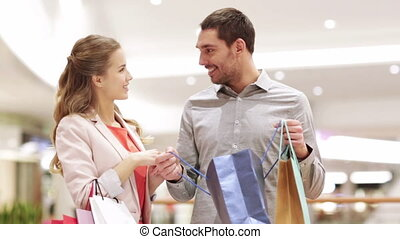 happy young couple with shopping bags in mall - sale,...
