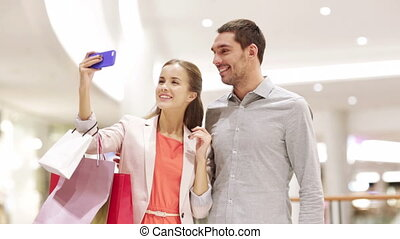 happy couple with smartphone taking selfie in mall - sale,...