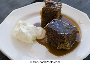 Sticky pudding and cream with silver spoon on wooden table