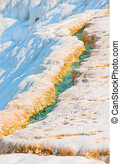rivulet with turquoise water on the mountain in Pamukkale