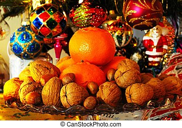 Mixed nuts and satsumas - Glass plate stand topped with...