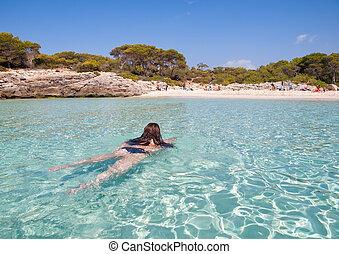 Woman bathing in Talaier creek, in Menorca, Spain.