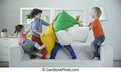 Misbehavior Holiday - Four kids playing on sofa pillow...