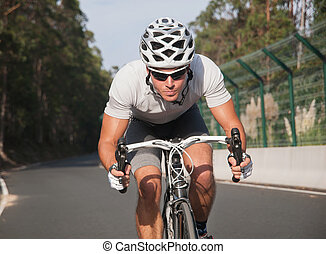 Cyclist portrait in action on the road in a sunny day.
