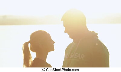 Couple in setting sun - Woman caring for her man against...
