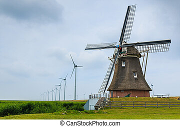 Old windmill and new wind turbines - Old historic dutch...