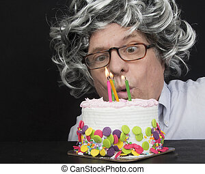 Mature Man Blowing Candles